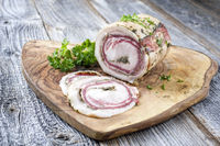 Traditional Italian panchetta arrotolata pork meat sliced and as piece with herbs offered as closeup on a rustic wooden board with copy space