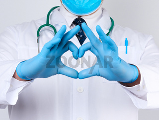 adult doctor man in a white medical coat with a stethoscope on his neck shows a heart gesture with his hands