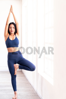 Asian sporty people practicing yoga tree pose portrait