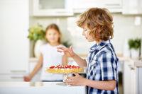 Junge kostet Kuchen mit Johannisbeeren