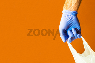 male hand holding shopping bag. plastic bag wearing blue gloves as protection for COVID-19 Corona