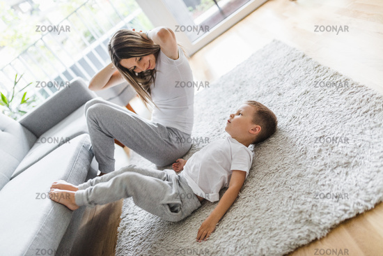 Mom with her young son working out in the living room