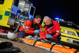 Paramedics giving firstaid to motorbike driver