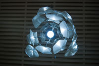 The interior design element is an original electric chandelier in the form of an exotic flower on a dark lattice ceiling