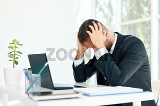 Stressed tired businessman sitting at the desk in creative office