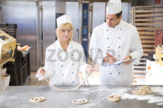Baker instructs apprentice how to form pretzel