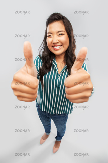 happy smiling asian woman showing thumbs up