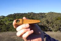 man smokes marijuana through a wooden smoking pipe in the open air.