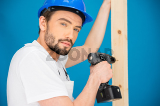 Carpenter drilling a hole in a plank of wood