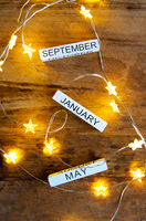 Perpetual calendar on a wooden table, different months against the background of garlands in the stars.