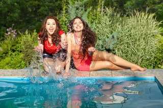 Two young women enjoy sunny day next to swimming pool