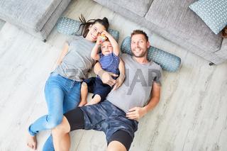 Eltern und Kind liegen auf dem Boden im Wohnzimmer