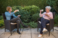 Senior woman and caregiver drinking coffee in the garden with safety discance