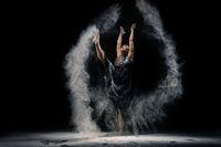 Graceful lady in underwear dancing with dust