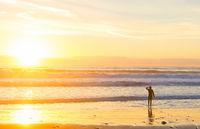 Surfer ocean beach sunset sunbeam