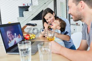 Fröhliches Kind mit Eltern im Videochat zum Geburtstag