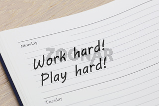Work hard play hard reminder note in a diary page