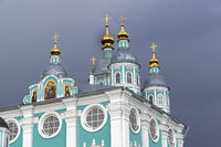 Domes of the Orthodox Cathedral in the background of a dark thundercloud.