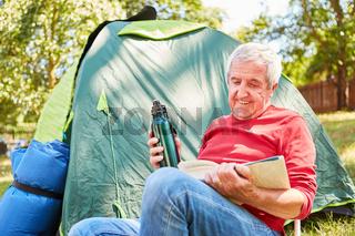 Senior Mann sitzt mit einem Buch vor seinem Zelt