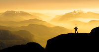 Spectacular mountain ranges silhouettes. Man reaching summit enjoying freedom. Sunrise with orange light.
