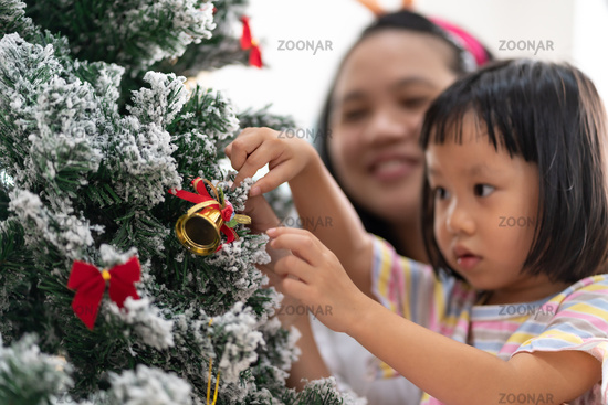 Little girl decorate christmas tree with ornament.