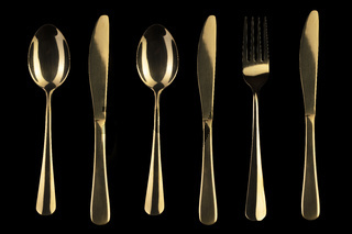 Gold knife and spoon and fork on a black background. Cutlery.