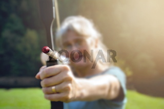 Woman ready to shoot at the target with a bow and arrow