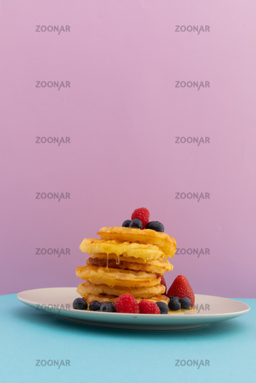 Stack of pancakes with berries and honey on blue and pink background