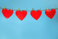 Four red hearts hanging on cord on blue background with copy space.