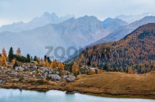 Overcast morning autumn alpine Dolomites mountain scene. Peaceful Valparola Path and Lake view, Belluno, Italy.