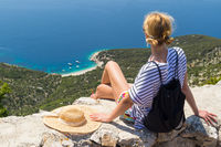 Active sporty woman on summer vacations sitting on old stone wall at Lubenice village, wearing straw hat and beach backpack enjoying beautiful coastal view of Cres island, Croatia