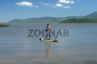 Young man practicing Stand Up Paddle on lake, yellow board, paddling. Paddleboarding.