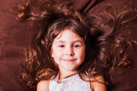 Face portrait of cute little girl with brown hair, lying on sofa. Kid dreams.