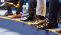 Detail of row of men's formal corporate business shoes. Business people sitting at seminar.