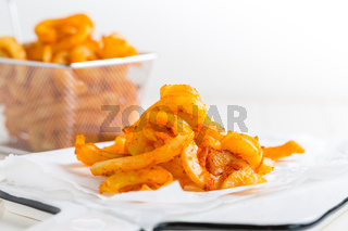 Spicy seasoned curly fries. Ready to eat on white background