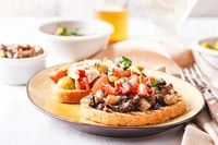 Delicious bruschettas with mushrooms, blue cheese, olives and tomatoes