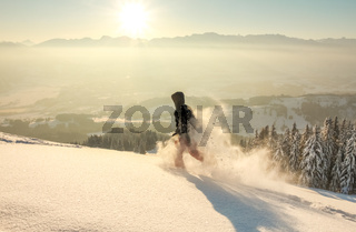 Happy Man with hood running in deep powder snow with snowshoes at sunrise. Snow is spraying and splashing. Allgau Alps, Bavaria, Germany.