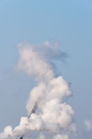 A single crane shrouded in smoke on a sunny day