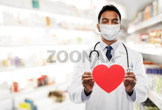 indian male doctor in mask with red heart shape