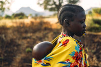 BOYA TRIBE, SOUTH SUDAN - MARCH 10, 2020: Girl in traditional colorful garment of Boya Tribe carrying baby on back on blurred background of savanna in South Sudan, Africa