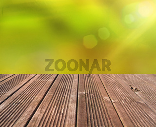 Emtpy wooden table with blurry nature background and flares