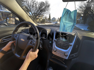 Calgary Alberta, Canada. Oct 17, 2020. A person driving a Chevrolet car on a sunny day, with a face mask hanging from the mirror. Cocept: Driving during Covid-19 pandemic