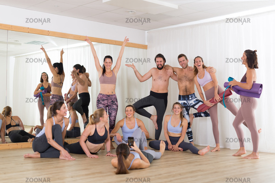 Group of young authentic real sporty attractive people in yoga studio having fun relaxing and socializing after hot yoga class. Healthy active lifestyle, working out in gym