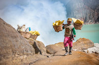 Kawah Ijen, Java, Indonesia - August 6, 2010: Sulfur miner carrying sulfur-laden baskets at Kawah Ijen volcano in East Java, Indonesia.