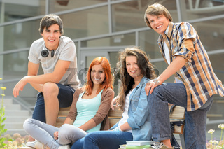 Group of students sitting bench front college