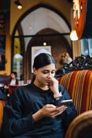 Pretty young girl resting on a big soft chair in a cafe, chatting on the phone
