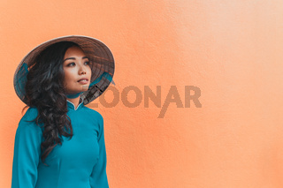 Portrait of young woman in traditional vietnamese dress and conical straw hat