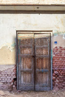 Closed abandoned wooden weathered door and shabby old grunge red bricks wall