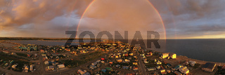 Rain falls as sun shines in the middle of the night at Kotzebue Alaska creating a beautiful contrast between the sunrise and storm