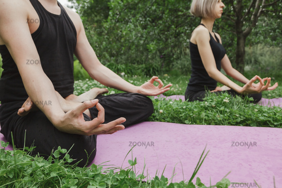 Man and woman doing yoga in lotus position sitting on grass